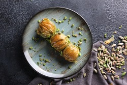 Oriental sweets. Pahlava with nuts, pistachio in a large dish on a black table. Turkish dessert. Background image, copy space, horizontal, top view, flatlay