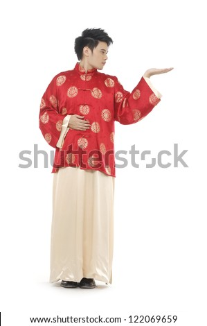Oriental young man with tradition clothing reaching out with his hands into the air