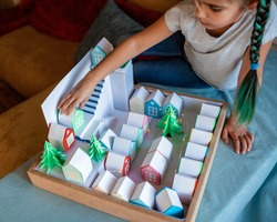 Origami advent calendar, Christmas village, paper craft. Cute girl looking upon tiny paper houses with number and paper green tree, seasonal activity with kids, indoor lifestyle