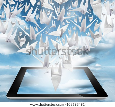 Origami Birds in flight on tablet pc computer on blue sky