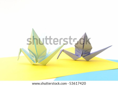 Origami birds over yellow paper. Child paper articles.