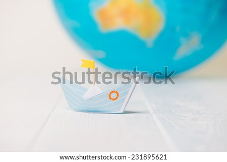 Origami boat, paper boat with a globe