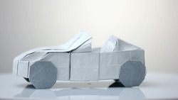Origami car model on white background. Exhibition of paper decorations.