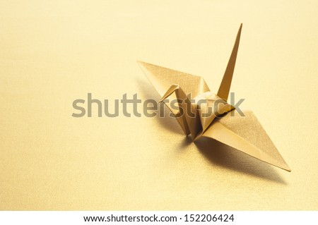 origami crane on gold background