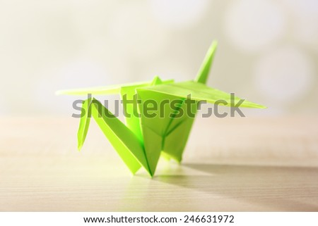 Origami crane on wooden table, on light background #246631972