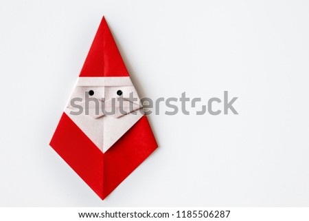 Origami for kids : 3D Big Santa Claus with mustache made from red folded paper on white background isolated.Natural light, copy space for text.Top view, flat lay.Easy to use for card. #1185506287