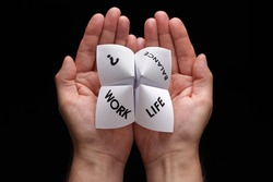 Origami fortune teller in cupped hands concept for work life balance choices