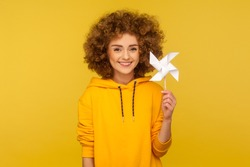 Origami hand mill. Portrait of happy curly-haired woman in urban style hoodie smiling carefree and holding paper windmill, pinwheel toy on stick. indoor studio shot isolated on yellow background
