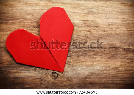 Origami heart on wooden background with copy-space
