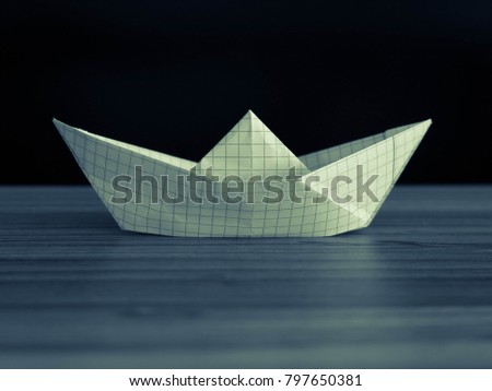 Origami paper boat on a background of blue and black #797650381