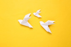 Origami paper doves on a yellow background. Peace symbol