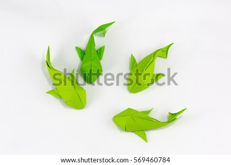 Origami paper green fishes on white background