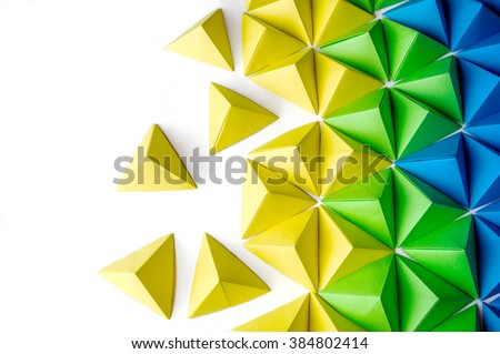 Stock Photo Origami tetrahedrons background. Futuristic polygonal composition with copy space on the left side.