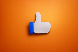 Origami thumbs up icon on orange background