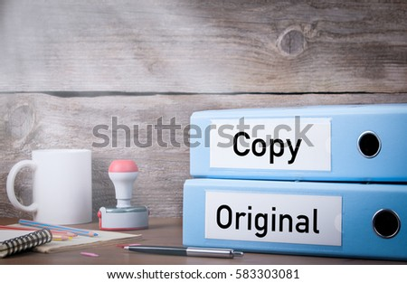 Original and Copy. Two binders on desk in the office. Business background