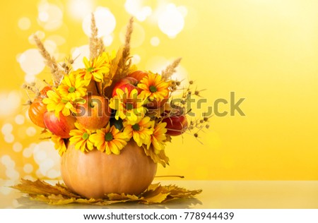 Original autumn bouquet of flowers, fruits and vegetables, decorated with spikelets and spines, in pumpkin, on yellow background #778944439