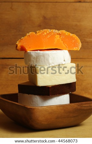 Original cheese in wooden bowl. Different kinds stacked