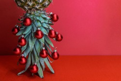 Original Christmas tree concept. Red shiny glass baubles hangs on the leaves of ripe pineapple standing upside down. Red background with copy space for your text.