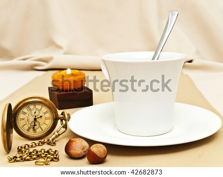 original decorated table serving with candle, nuts and old pocket watch near cup at beige