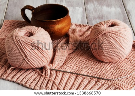 Original exclusive knitted pattern of delicate pink yarn and beautiful clay cup on light wooden background. Concept — hobbies and hobbies.