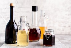 Original glass bottles with different vinegar on a marble table against a background of a white brick wall. Copy space. Horizontal.