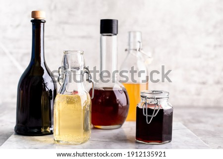 Original glass bottles with different vinegar on a marble table against a background of a white brick wall. Copy space. Horizontal. Foto stock ©
