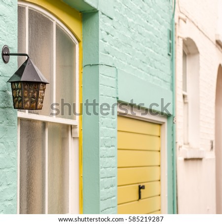 original lamp on the facade of the building, artistic lamps in the background painted brick facades of buildings, interesting colors Click connection bright green and beige with elements of yellow, #585219287