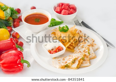 original Mexican quesadilla de pollo with nachos  served with gazpacho soup and watermelon ,with fresh vegetables on background