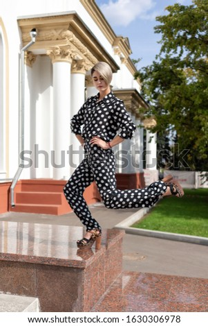 original pose in a standing pose on one leg. beautiful European girl in a black suit with white spots in high heels, pants and a shirt.
