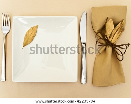 original table serving with golden bay leaves in serviette and cord near plate, knife and fork at beige
