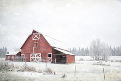 Original textured vintage style photograph of an old red barn on a winter day in snow