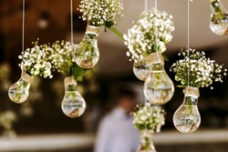 Original wedding floral decoration in the form of mini-vases and bouquets of flowers hanging from the ceiling