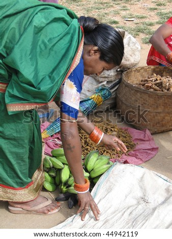 ORISSA, INDIA - NOV 11 : Indian woman in saree chooses fruit at weekly market on Nov 11, 2009 in Orissa, India