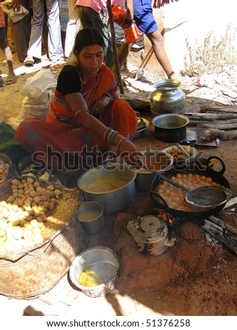 ORISSA INDIA - NOV 10  - Woman prepares fried food for snacks at a  weekly market on Nov 10, 2009 in Orissa, India - stock photo