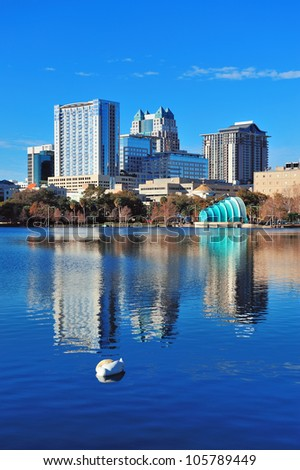 Orlando Lake Eola in the morning with a group of urban skyscrapers and clear blue sky with swan sleeping in water.