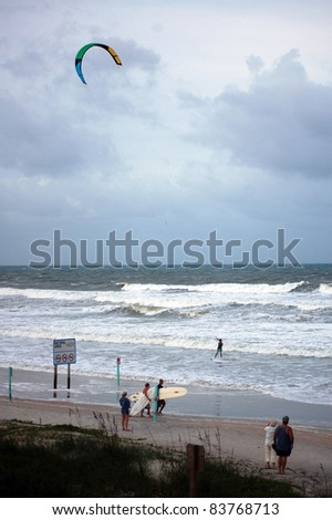 ORMOND BEACH, FL - AUGUST 25:  Spectators watch an unidentified kite-boarder as Hurricane Irene passes off the coast on August 25, 2011, in Ormond Beach, Florida. Two unidentified surfers leave. - stock photo