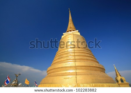 Ornament : Thailand's gold pagoda landmark, Golden Mount, with thai flag against blue sky at Wat sraket in Bangkok, Thailand