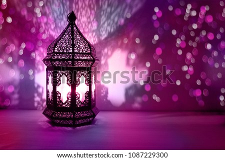 Ornamental Arabic lantern with burning candle glowing at night and glittering colorful bokeh lights. Festive greeting card, invitation for Muslim holy month Ramadan Kareem. Blurred party background #1087229300
