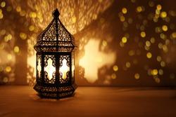 Ornamental Arabic lantern with burning candle glowing at night and glittering golden bokeh lights. Festive greeting card, invitation for Muslim holy month Ramadan Kareem. Dark background.