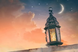 Ornamental Arabic lantern with burning candle glowing at night. Festive greeting card, invitation for Muslim holy month Ramadan Kareem.