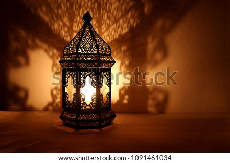 Ornamental Arabic lantern with burning candle glowing at night.. Golden festive greeting card, invitation for Muslim holy month Ramadan Kareem. Modern blurred party background. #1091461034