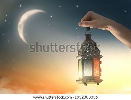 Ornamental Arabic lantern with burning candle glowing in hand. Festive greeting card, invitation for Muslim holy month Ramadan Kareem.