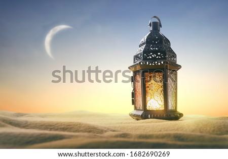 Ornamental Arabic lantern with burning candle glowing on sand. Festive greeting card, invitation for Muslim holy month Ramadan Kareem.