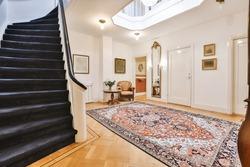 Ornamental carpet placed on floor near stairway in vintage hallway of elegant house