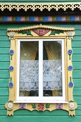 Ornamental carved window, frame with owl on vintage wooden rural house in Pereslavl-Zalessky town, Yaroslavl region, Russia. Russian traditional national folk style in architecture. Countryside