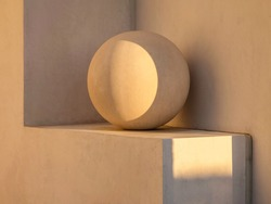 Ornamental concrete sphere on a small exterior ledge of a house at sunset