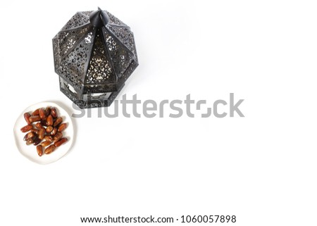 Ornamental dark Moroccan, Arabic lantern and plate with date fruits on the white table. Greeting card for Muslim holy month Ramadan Kareem. Festive background. Empty space. Flat lay, top view. #1060057898