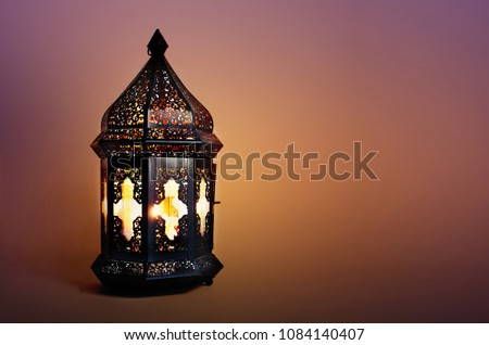Ornamental dark Moroccan, Arabic lantern on the table. Burning candle in the night. Greeting card for Muslim community holy month Ramadan Kareem. Festive blurred background. #1084140407