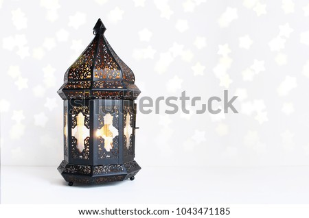 Ornamental dark Moroccan, Arabic lantern on the white table. Burning candle, glittering bokeh lights stars. Greeting card for Muslim community holy month Ramadan Kareem. Festive background. #1043471185