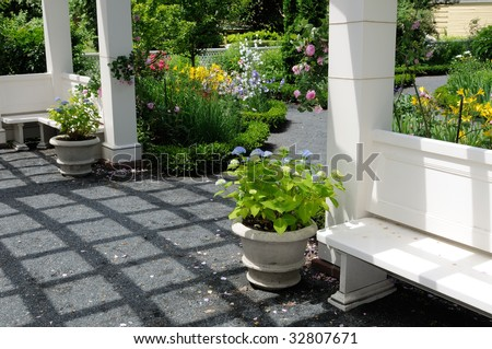 Ornamental garden and pergola. Bench, flower pots, footpath